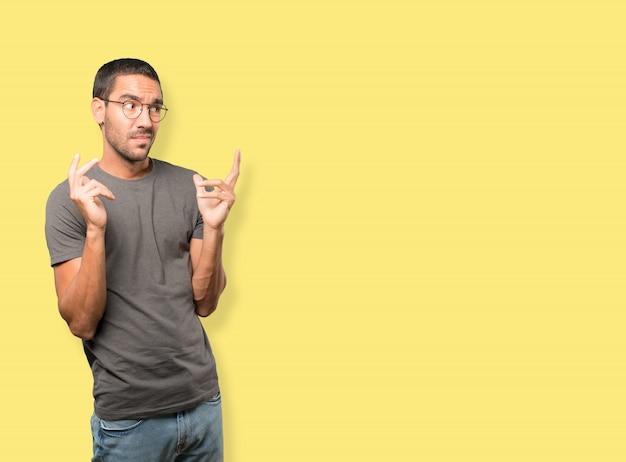 Hombre joven preocupado haciendo un gesto de confusión