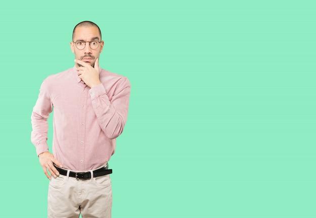Hombre joven preocupado que presenta contra el fondo