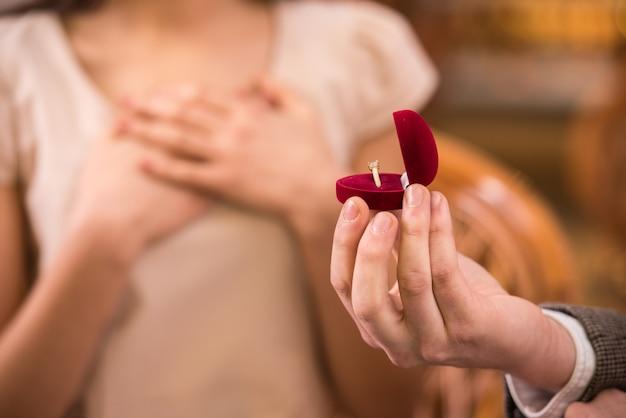 El hombre joven está presentando el anillo de compromiso a su novia.