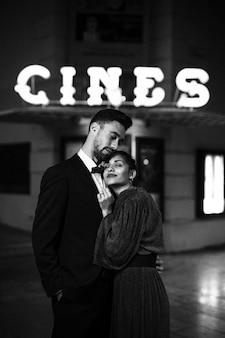 Hombre joven que abraza a la mujer atractiva encantadora en la calle