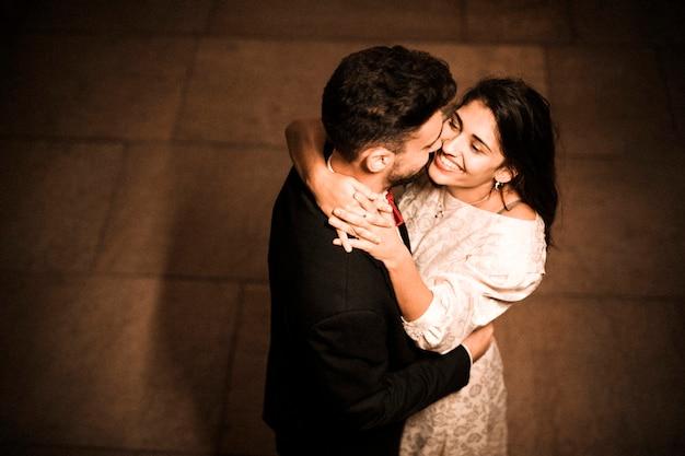 Hombre joven que abraza a la mujer feliz