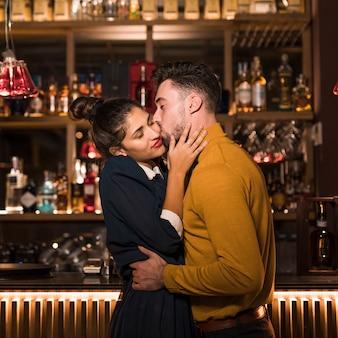 Hombre joven que abraza y que besa a la mujer encantadora en la barra