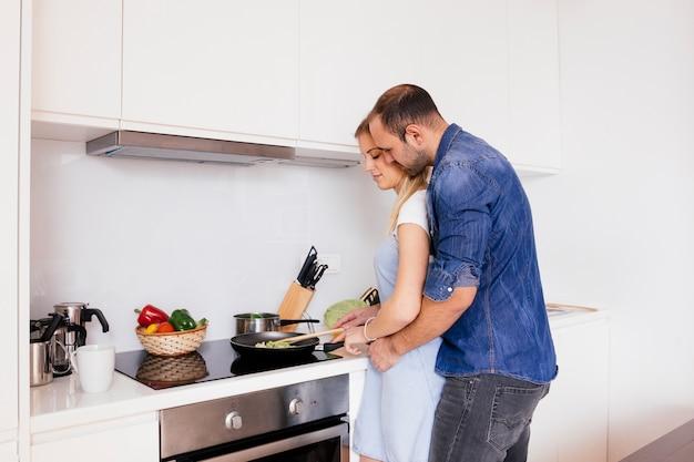 Hombre joven que abraza a su esposa que prepara la comida en la cocina