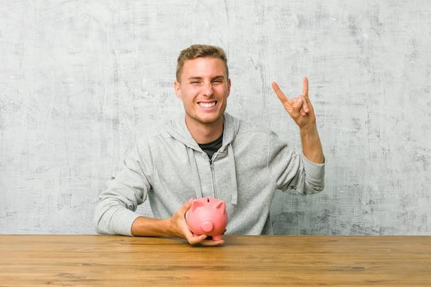 Hombre joven que ahorra dinero con una hucha que muestra un gesto de cuernos como un concepto de revolución.