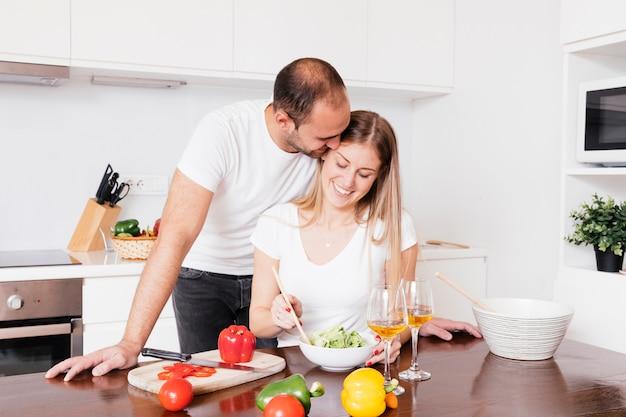 Hombre joven que ama a su esposa que prepara la ensalada en la cocina