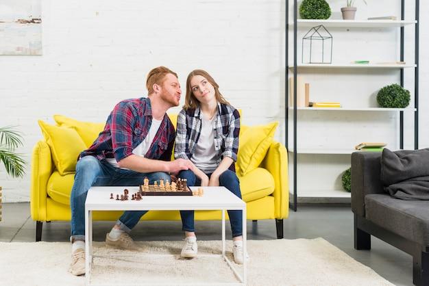Hombre joven que ama a su novia que se sienta en el sofá amarillo que juega a ajedrez en casa