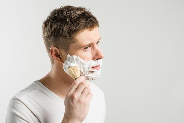 Hombre joven que aplica espuma en mejillas con el cepillo sobre el fondo blanco