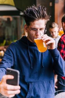 Hombre joven que bebe el vidrio de cerveza que toma el selfie en smartphone