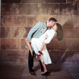 Hombre joven que besa a la mujer en calle