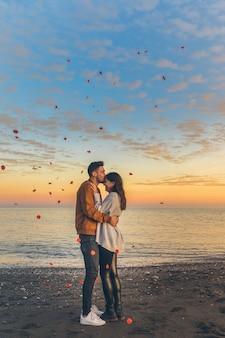 Hombre joven que besa a la mujer en la frente en orilla de mar