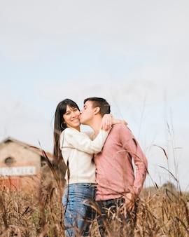Hombre joven que besa a la mujer en mejilla