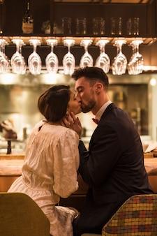 Hombre joven que besa a la mujer y que se sienta en el contador de la barra