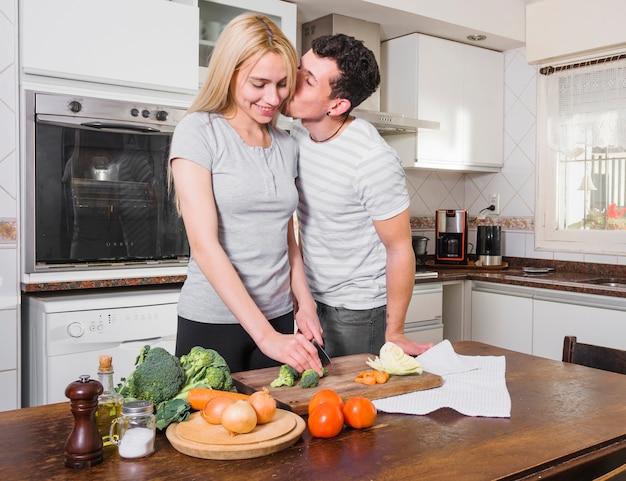 Hombre joven que besa a su esposa que corta la verdura en tajadera