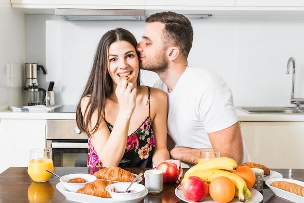 Hombre joven que besa a su novia comiendo galletas con frutas y croissant en la mesa en la cocina