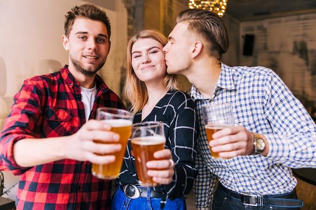 Hombre joven que besa a su novia mientras tuesta los vasos de cerveza con un amigo