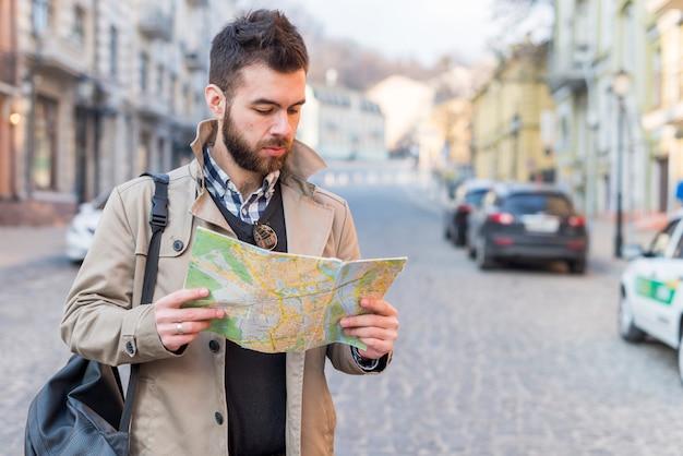 Hombre joven que busca la manera en el mapa de destino; disfrutando de vacaciones