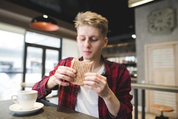 Hombre joven que cena el emparedado de panini en restaurante.