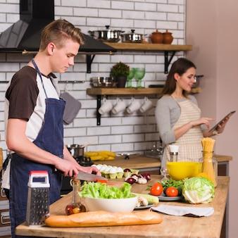Hombre joven que cocina la comida con la novia que usa la tableta