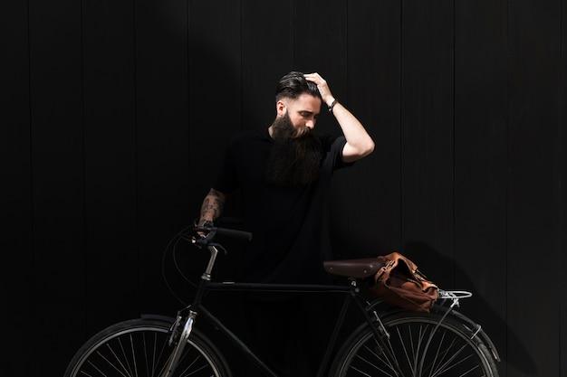 Hombre joven que coloca la bicicleta cercana con su mano en la cabeza contra fondo negro