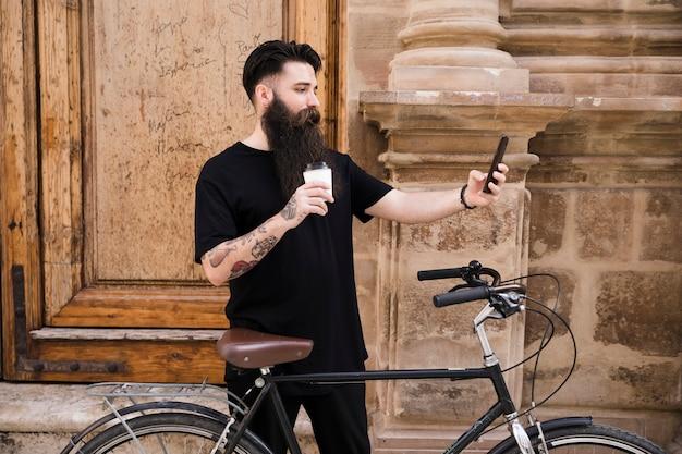 Hombre joven que se coloca con la bicicleta delante de la puerta de madera que toma el selfie en el teléfono móvil