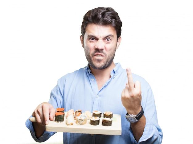 Hombre joven que come sushi en el fondo blanco