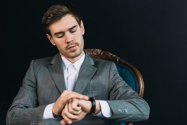 Hombre joven que comprueba tiempo en su reloj contra fondo negro