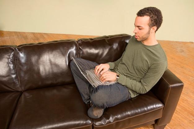 Hombre joven que computa en el sofá