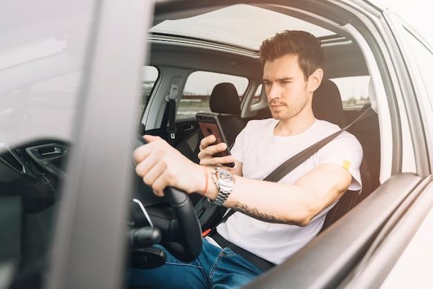 Hombre joven que conduce el coche usando smartphone