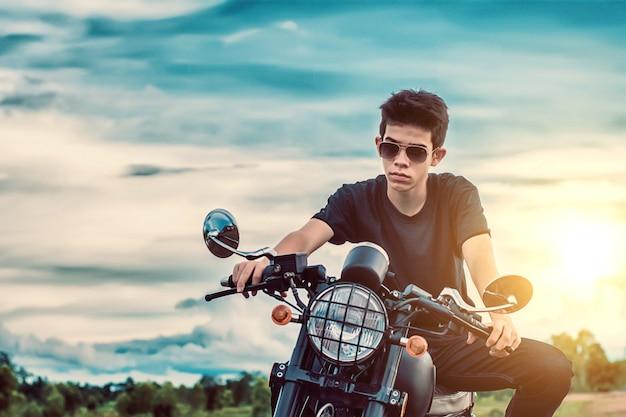 Hombre joven que conduce la moto al lado del lago natural y hermoso.
