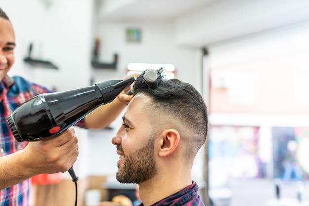 Hombre joven que consigue un peinado en una barbería.