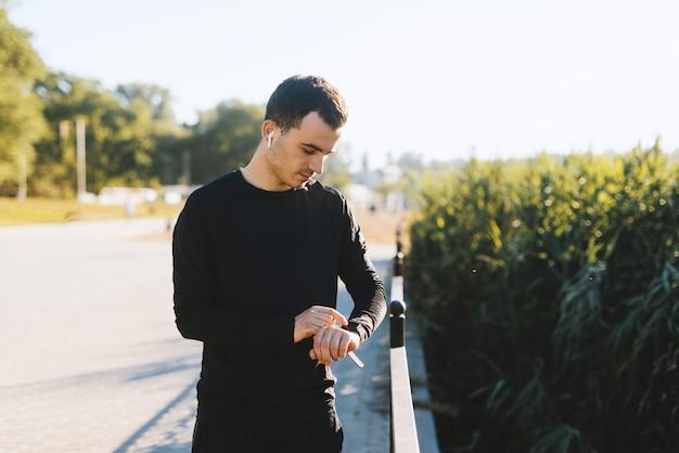 Hombre joven que controla su ritmo cardíaco en su reloj elegante al aire libre en el parque después de correr.