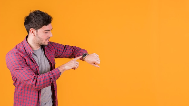 Hombre joven que controla el tiempo en su reloj de pulsera contra el fondo naranja