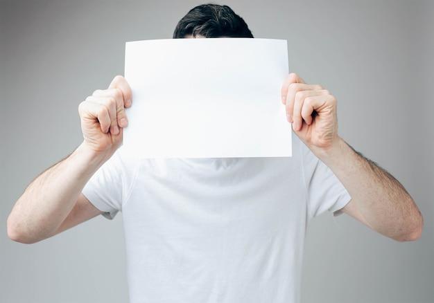 Hombre joven que cubre su rostro con una hoja de papel en blanco blanco