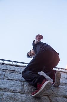 Hombre joven que cuelga en la pared y que intenta subir mientras que hace parkour.