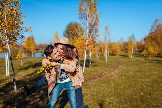 Hombre joven que da a su novia a cuestas en el bosque de otoño gente divirtiéndose