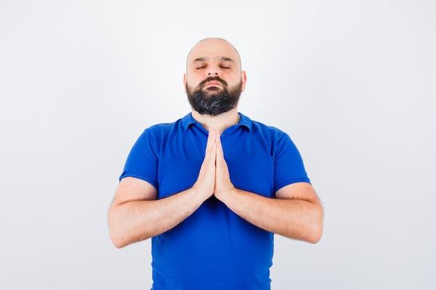 Hombre joven que desea en camisa azul y parece esperanzado. vista frontal.
