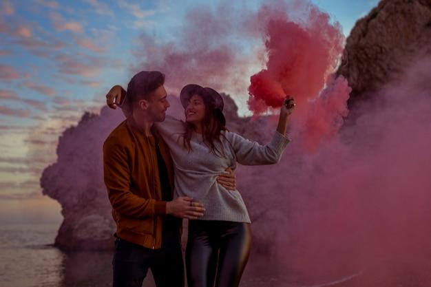 Hombre joven que detiene a la mujer con la bomba de humo rosada en orilla de mar