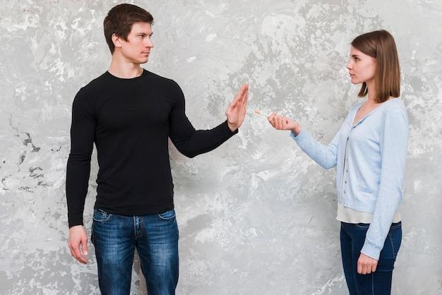 Hombre joven que dice no a la mujer que ofrece el cigarrillo que se coloca cerca de la pared vieja