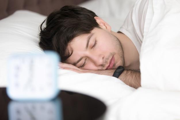 Hombre joven que duerme al lado del reloj de alarma que lleva pulsera inteligente