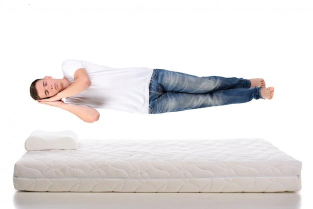 Hombre joven que duerme en un colchón que vuela durante sueño.