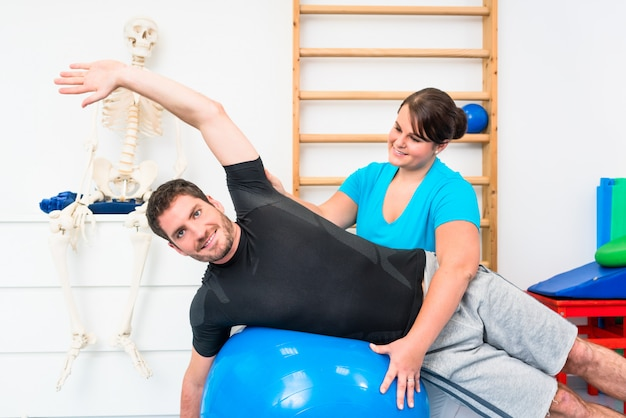 Hombre joven que ejercita en bola suiza en fisioterapia