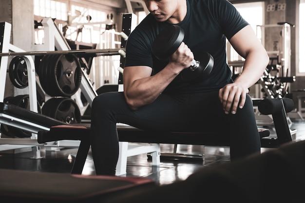 Hombre joven que ejercita los músculos del edificio en el gimnasio