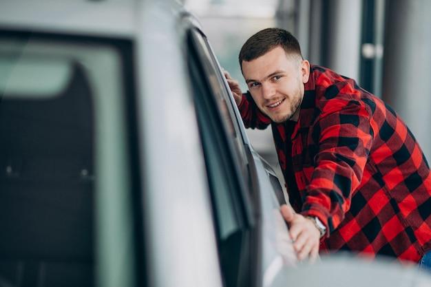 Hombre joven que elige un coche en una sala de exposición de automóviles Foto gratis