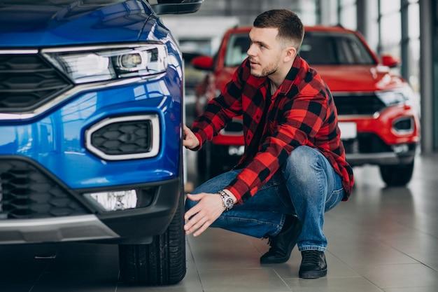 Hombre joven que elige un coche en una sala de exposición de automóviles