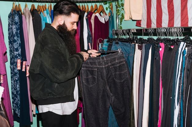 Hombre joven que elige los pantalones vaqueros que cuelgan en el carril en la tienda de ropa