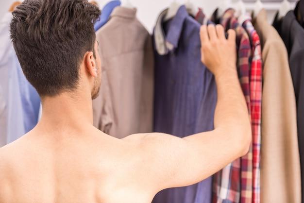 Hombre joven que elige la ropa en un estante en guardarropa.