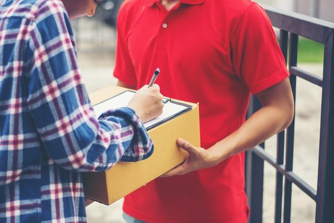 Hombre joven que entrega el paquete al cliente en casa. entrega