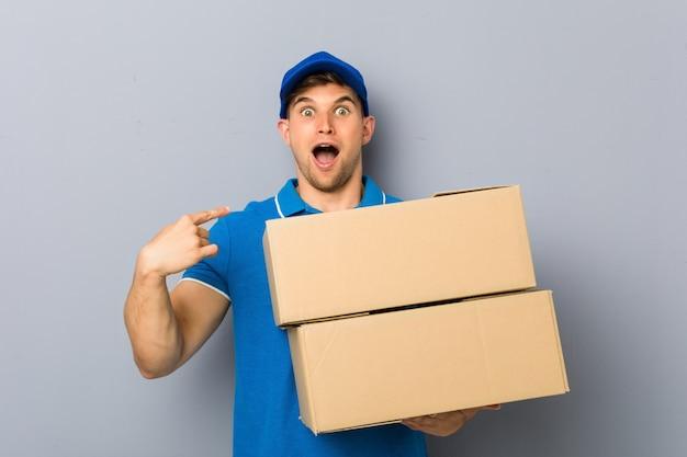 El hombre joven que entregaba paquetes sorprendió apuntándose a sí mismo, sonriendo ampliamente.