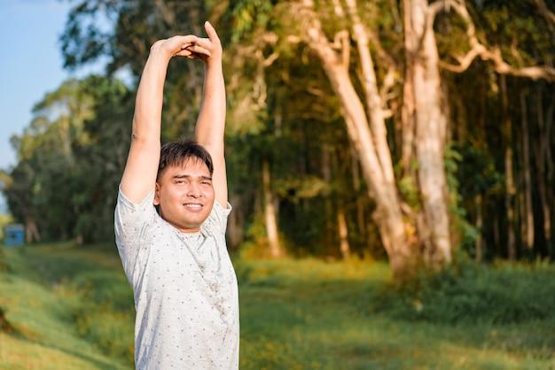 Hombre joven que estira el cuerpo después de correr en el parque