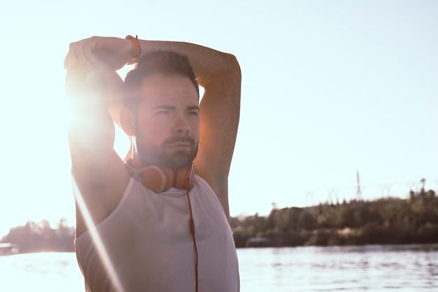Hombre joven que estira sus brazos con los auriculares puestos.